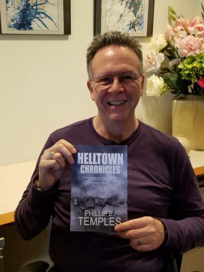 Phil Temples holding proof copy of Helltown Chronicles