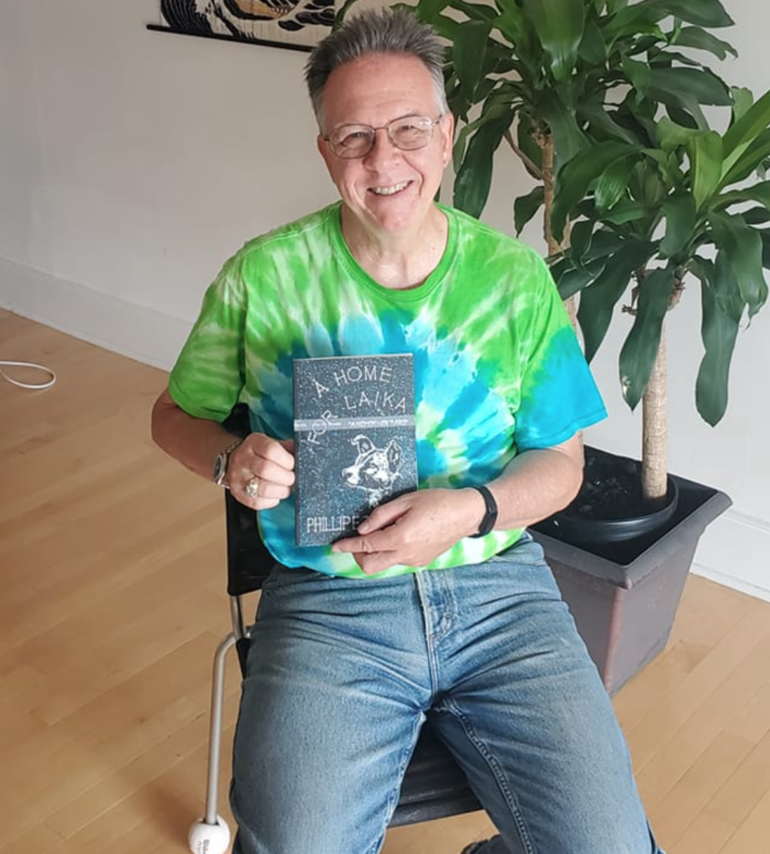 Phil Temples holding proof copy of Home for